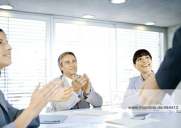 Business-Team applaudiert Kollegen im Konferenzraum