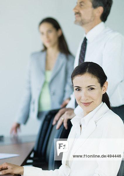 Drei Geschäftskollegen lächeln vor der Kamera  Fokussierung auf den Vordergrund