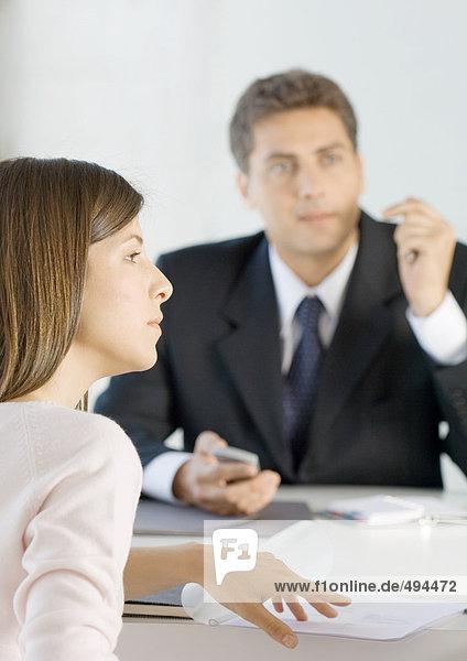 Verkäufer und Frau am Tisch sitzend mit Dokumenten  aus dem Rahmen schauend