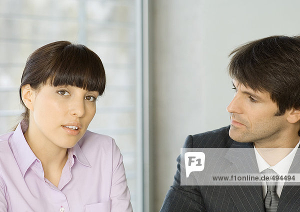 Woman speaking with businessman  looking at camera