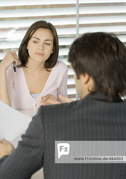Woman sitting across from businessman