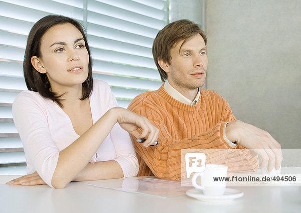 Junges Paar am Tisch sitzend mit Tassen Kaffee