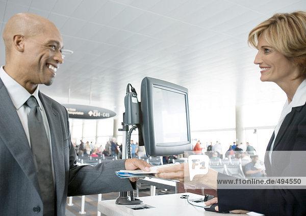 Flugbegleiter bei der Abgabe des Passagiertickets am Check-in-Schalter