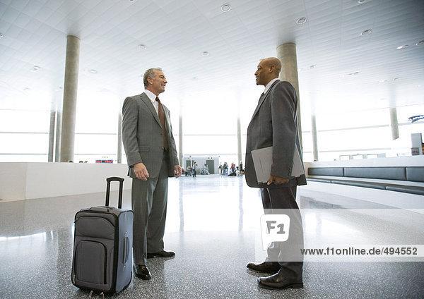 Zwei Geschäftsleute im Gespräch in der Flughafenhalle