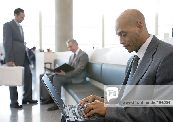 Businessman using laptop in airport lounge area