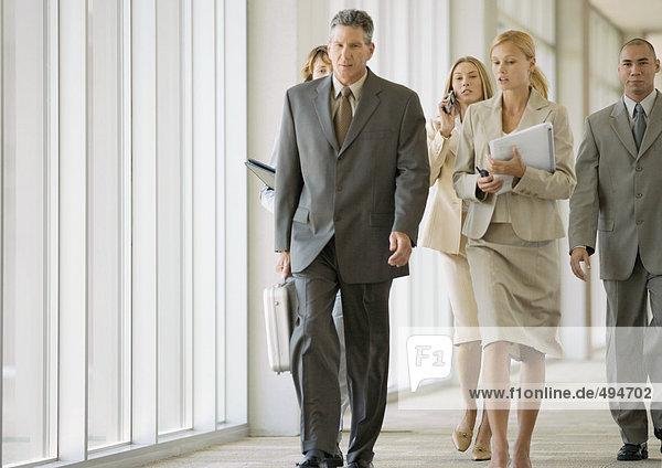 Führungskräfte gehen durch den Flur des Bürogebäudes