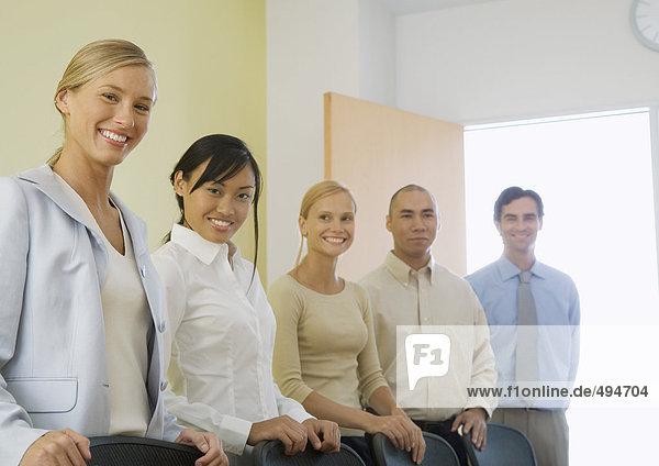 Gruppe junger Führungskräfte  die im Vorstandszimmer stehen