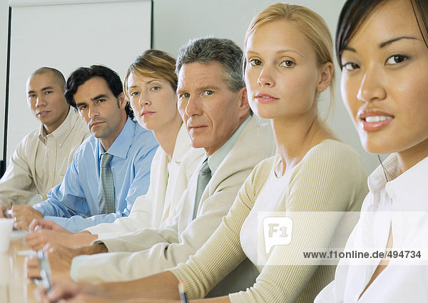 Row of business people sitting at table