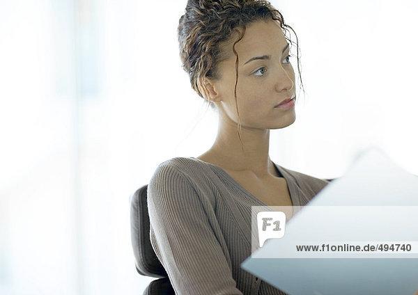 Junge Geschäftsfrau schaut aus der Akte auf Junge Geschäftsfrau schaut aus der Akte auf