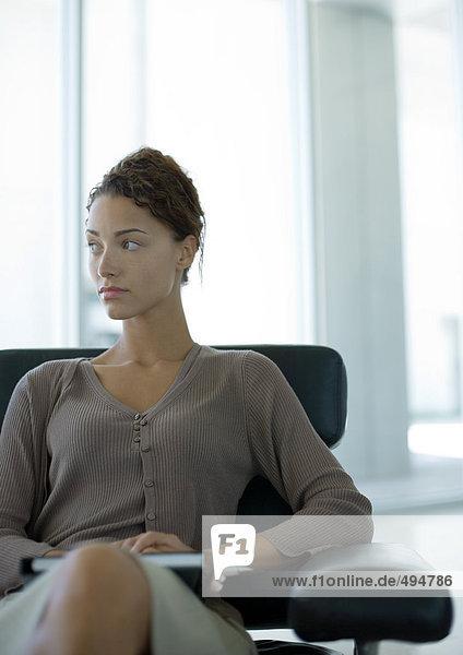 Frau sitzt in der Büro-Lobby Frau sitzt in der Büro-Lobby
