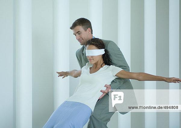 Geschäftsmann fängt mit verbundenen Augen Frau Geschäftsmann fängt mit verbundenen Augen Frau
