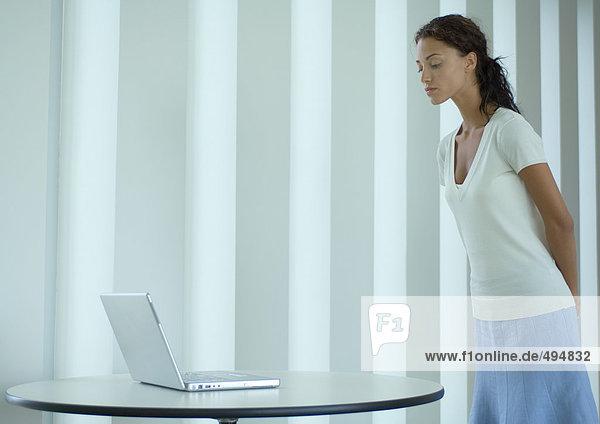 Frau stehend  auf den Laptop schauend Frau stehend, auf den Laptop schauend