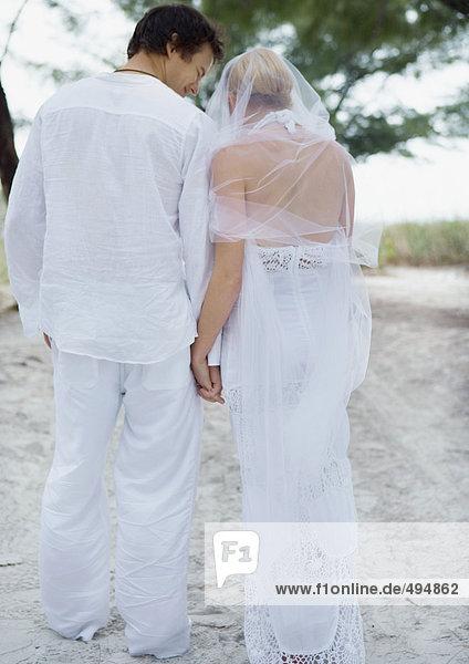 Braut und Bräutigam gehen am Strand  Händchen haltend  Rückansicht