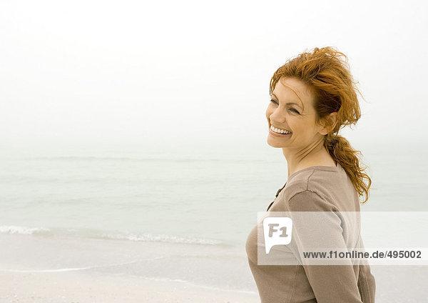 Frau lächelt am Strand