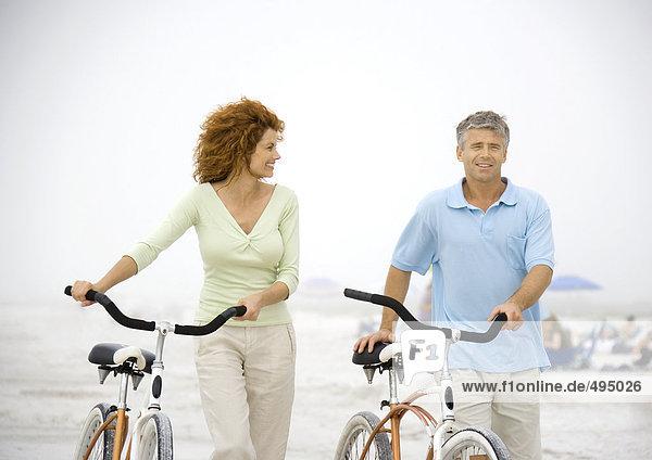 Paar Wanderungen mit dem Fahrrad am Strand