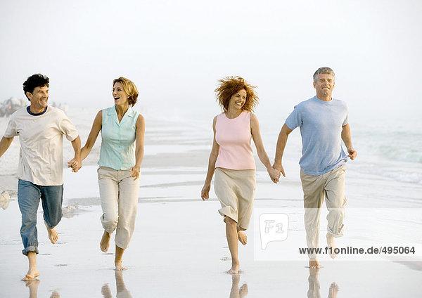Zwei reife Paare  die am Strand laufen