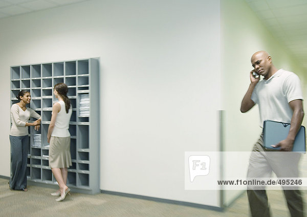 Büroszene  zwei Frauen sprechen über Briefkästen  während der Mann mit dem Handy durch den Flur geht.