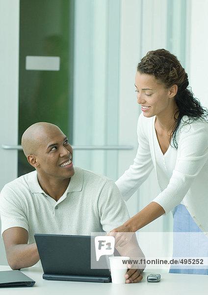 Frau hilft männlichen Kollegen Frau hilft männlichen Kollegen