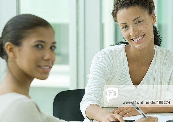 Zwei weibliche Mitarbeiter  lächelnd vor der Kamera Zwei weibliche Mitarbeiter, lächelnd vor der Kamera