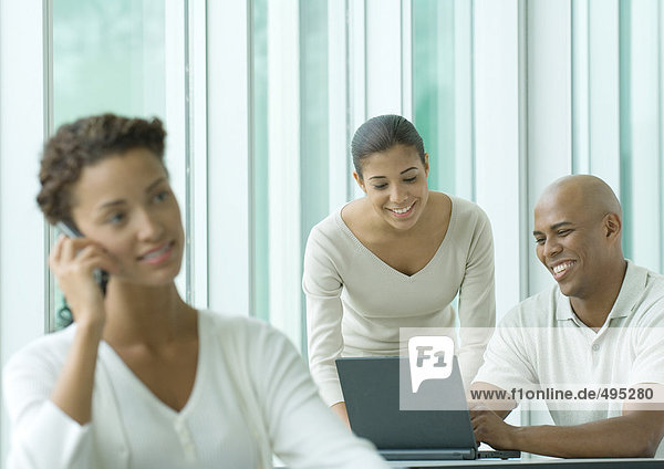 Büroszene  zwei Mitarbeiter nutzen Laptop  während Frau im Vordergrund Handy benutzt Büroszene, zwei Mitarbeiter nutzen Laptop, während Frau im Vordergrund Handy benutzt