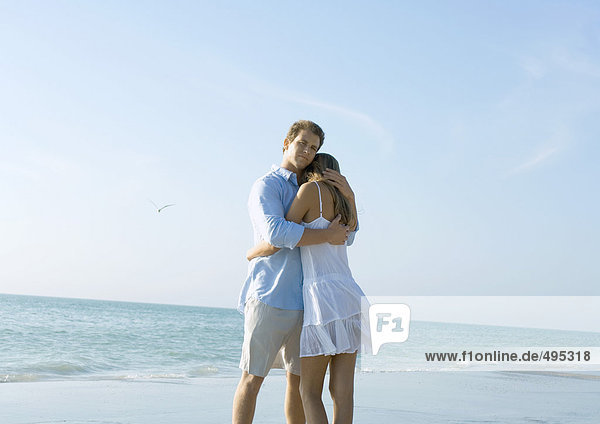 Paar am Strand stehend  umarmend