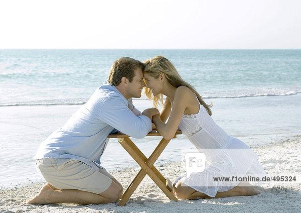 Paar kniend am Strand  Kopf an Kopf