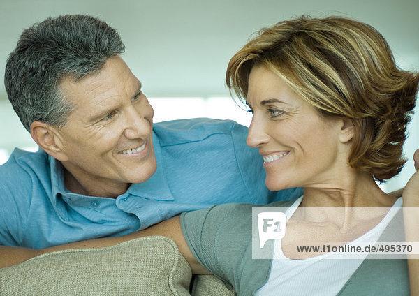 Ein reifes Paar lächelt sich an.