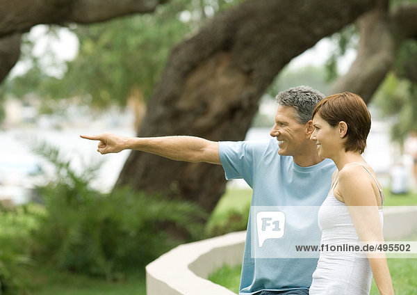 Mature couple  pointing toward distance  side view