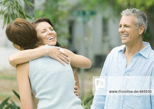 Zwei Frauen  die sich umarmen  während der Mann zusieht.