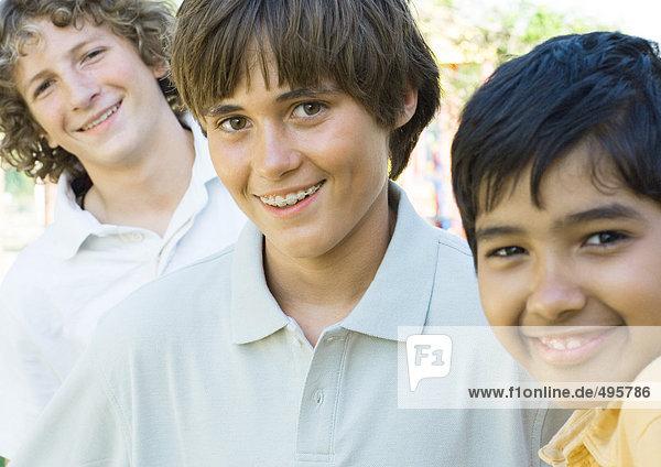 Three preteen boys  smiling
