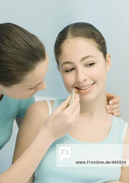 Teenage girl putting lipstick on friend