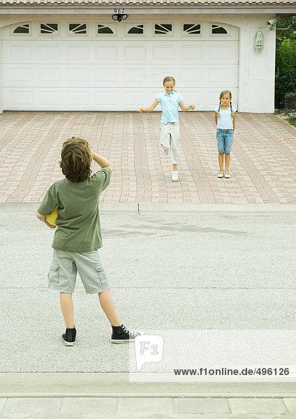 Zwei Mädchen spielen in der Einfahrt  während der Junge von der Straße aus zuschaut.