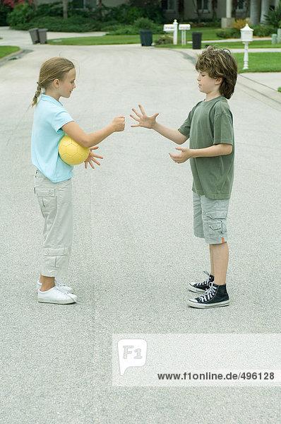 Junge und Mädchen spielen Steinpapierschere in der Wohnstraße
