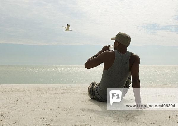 Man drinking water on beach