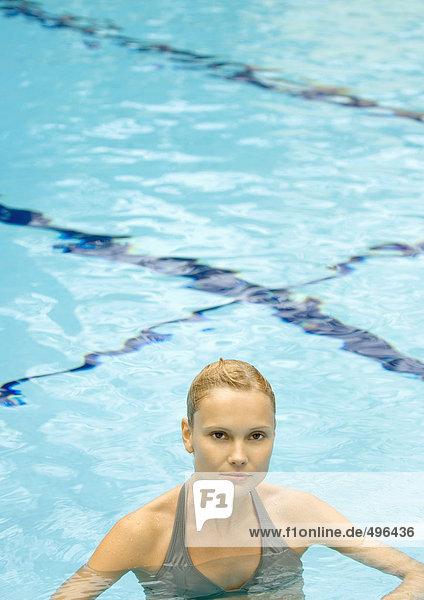 Frau steht im Pool und schaut in die Kamera.