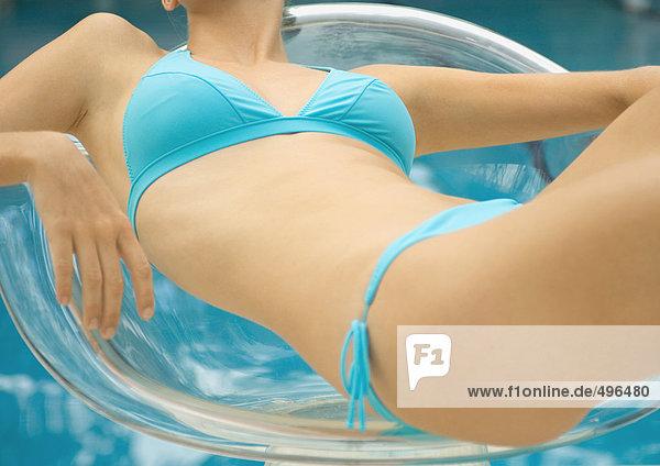 Frau im Bikini-Lounging im transparenten Stuhl