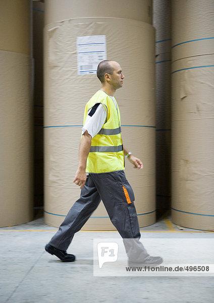 Fabrikarbeiter geht an Papierrollen vorbei