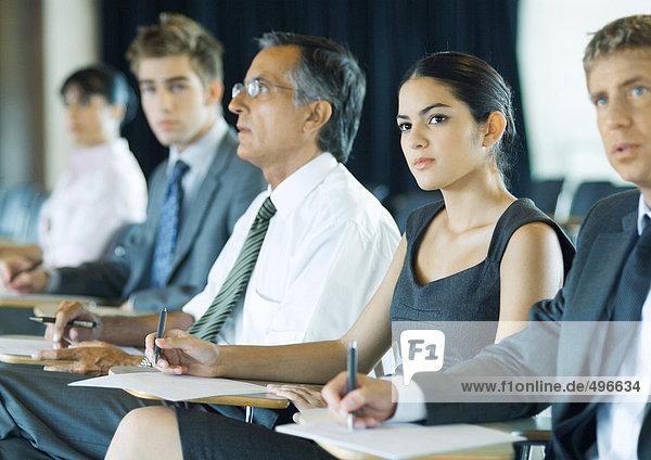 Geschäftsleute sitzen  Notizen machen  aufmerksam aus dem Rahmen schauen