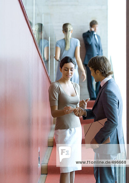 Businessman and woman exchanging business card