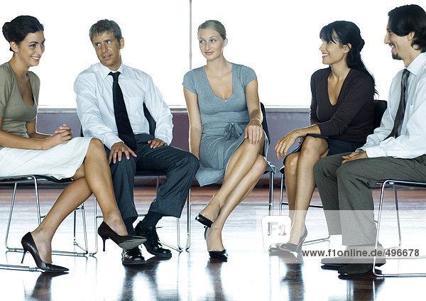 Geschäftsleute auf Stühlen sitzend  mit Besprechung  volle Länge