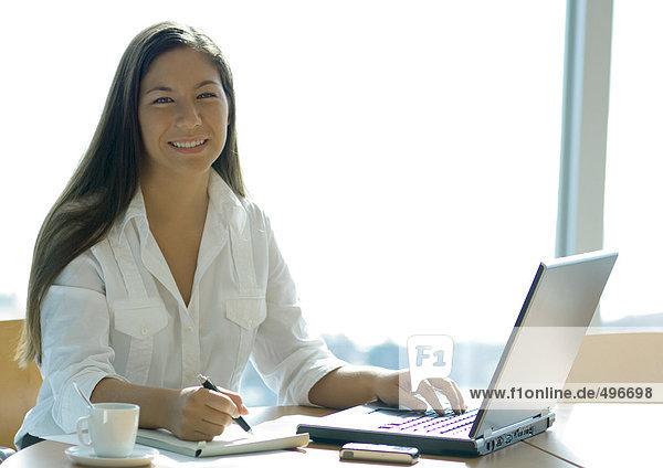 Geschäftsfrau bei der Arbeit mit dem Laptop