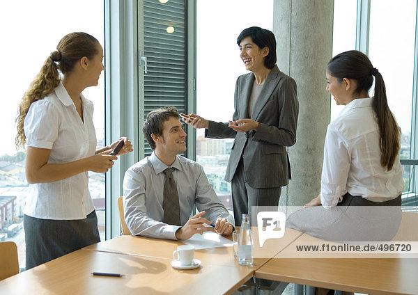 Business colleagues standing at sitting at table  discussing