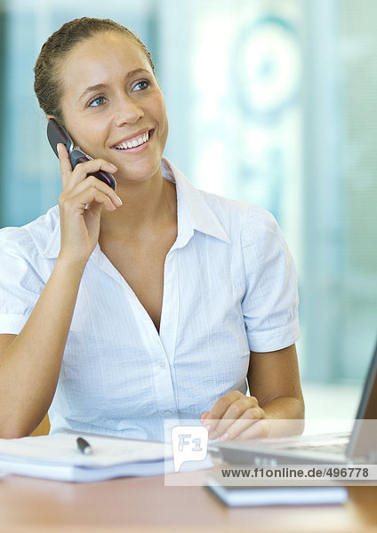 Businesswoman sitting at desk  using cell phone