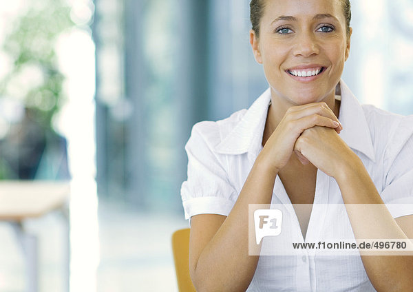 Businesswoman with hands clasped under chin  smiling  portrait