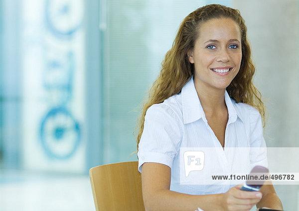 Businesswoman holding cell phone  portrait