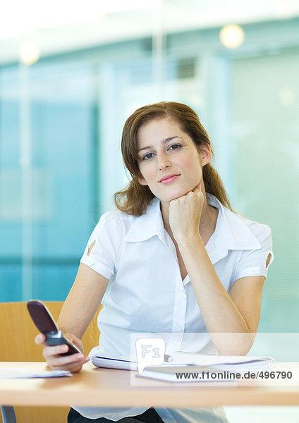 Büroangestellte  die am Schreibtisch sitzt und ein Handy hält