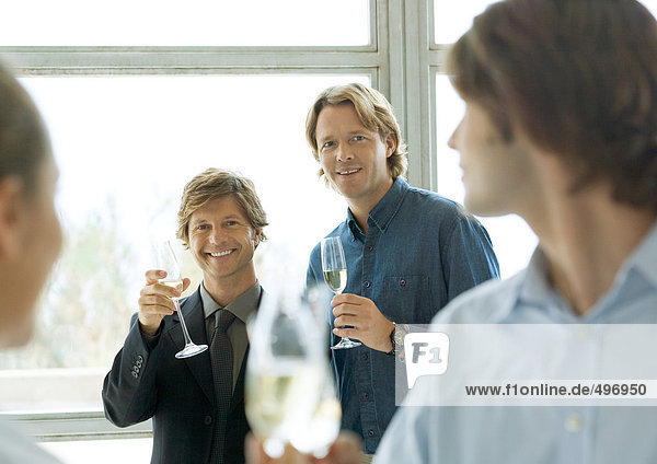 Men holding up glasses of champagne during cocktail party