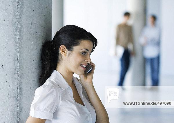 Junge Frau mit Handy  Kollegen im Hintergrund