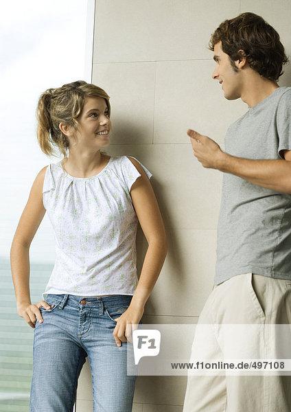 Junger Mann und Frau lehnen sich an die Wand  reden und lächeln
