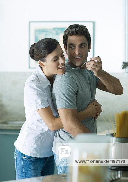 In der Küche hält die Frau den Mann um die Taille  während der Mann mit einem Löffel nach hinten greift  damit die Frau schmeckt.